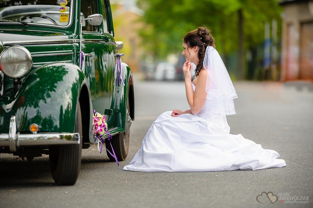 Die wunderschöne Braut betrachtet sich im Glanz des Oldtimerhochzeitsautos an der Alten Pulverfabrik in Berlin Spandau fotografiert vom Hochzeitsfotograf Berlin Marc Birkhoelzer www.hochzeitsaufnahmen.com