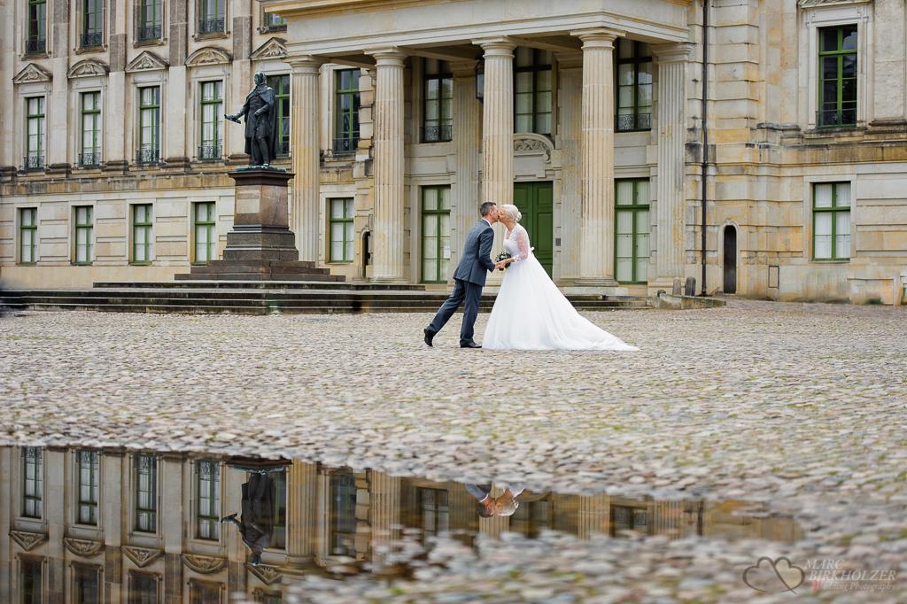 Ein Hochzeitskuss gespiegelt im Glanz einer Pfütze vor dem Schloss Ludwigslust fotografiert vom Hochzeitsfotograf Berlin Marc Birkhoelzer www.hochzeitsaufnahmen.com
