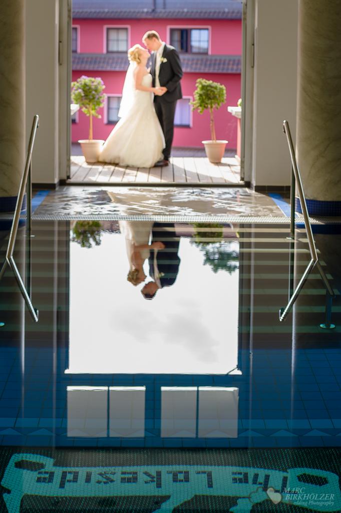 Das Hochzeitspaar spiegelt sich im Wasser des Schwimmbades im Lakesidehotel Strausberg bei den Portraitaufnahmen fotografiert vom Hochzeitsfotograf Berlin Marc Birkhoelzer www.hochzeitsaufnahmen.com