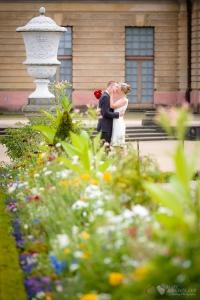 Hochzeitspaar küsst sich hinter einer romatischen Blumenwiese in Berlin Charlottenburg aufgenommen vom Hochzeitsfotograf Berlin Marc Birkhoelzer www.hochzeitsaufnahmen.com