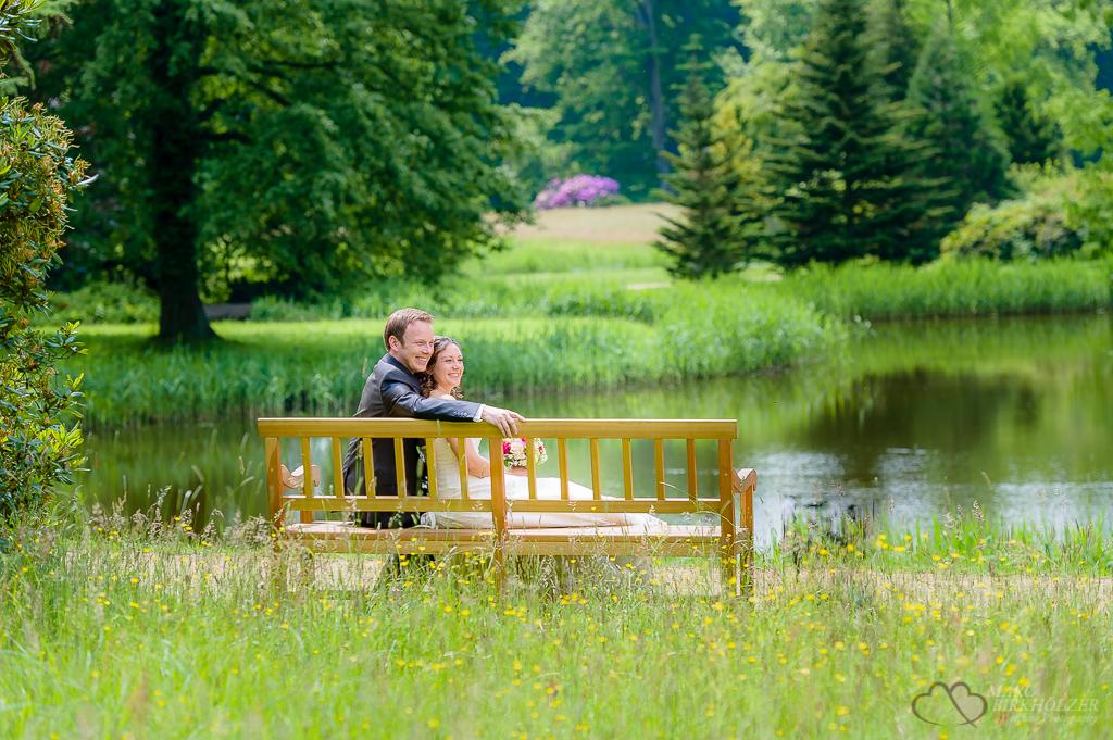 Brautpaar-Fotosession auf einer Parkbank im Schloßgarten des Schloss Wiesenburg professionell fotografiert vom Hochzeitsfotografen Berlin Marc Birkhoelzer www.hochzeitsaufnahmen.com