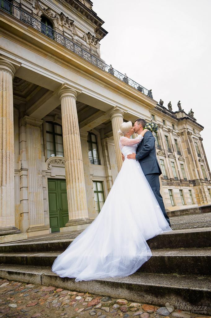Beim Portraitshooting lang ausgebreitetes Hochzeitskleid aufgenommen vor dem Schloss Ludwigslust durch den Hochzeitsfotograf Berlin Marc Birkhoelzer www.hochzeitsaufnahmen.com