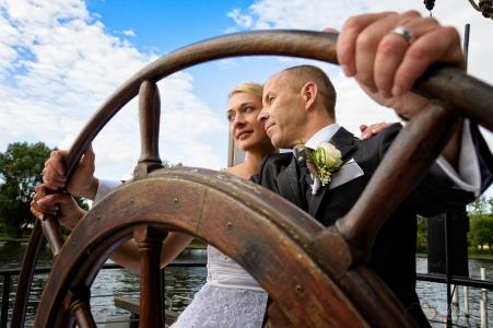 Der Bräutigam übernimmt das Ruder auf dem Restaurantschiff arsVivendi an der Freiheit fünfzehn in Berlin Köpenick aufgenommen durch den Hochzeitsfotografen Berlin Marc Birkhoelzer www.hochzeitsaufnahmen.com