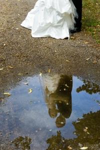 Ein Hochzeitsfoto bei Regen während sich das Hochzeitspaar in einer Pfütze spiegelt aufgenommen durch den Hochzeitsfotograf Berlin Marc Birkhoelzer www.hochzeitsaufnahmen.com