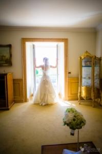 Im Schloss Diedersdorf schaut die Braut aus dem Zimmerfenster fotografiert vom Hochzeitsfotograf Marc Birkhoelzer www.hochzeitsaufnahmen.com