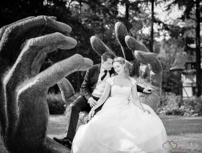 Das Hochzeitspaar in einer Bronzeplastik in Gestalt zweier Hände im Garten des idyllisch gelegenen Gut Klostermühle Alt Madlitz fotografiert vom Hochzeitsfotograf Berlin Marc Birkhoelzer www.hochzeitsaufnahmen.com