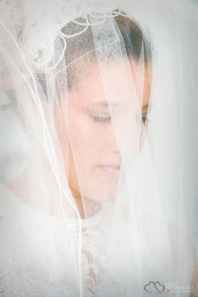 Die Braut mit Brautschleier in einem Moment der Ruhe in Gedanken versunken und fotografiert vom Hochzeitsfotograf Berlin Marc Birkhoelzer www.hochzeitsaufnahmen.com