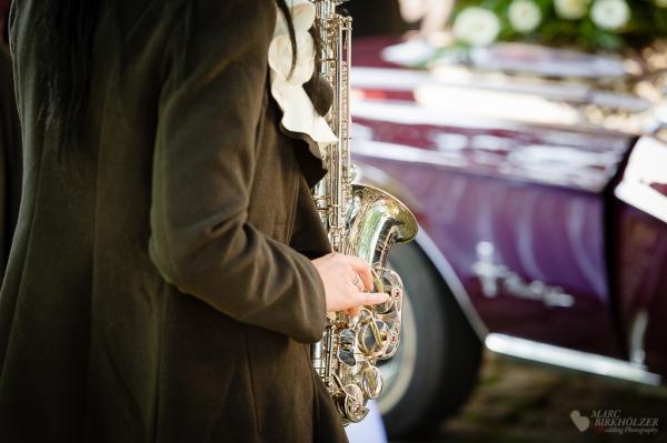 Saxophonmusik zur Ankuft des Hochzeitspaares in einem Ford Mustang am Landgasthof zum Mühlenteich in Eggersdorf fotografiert vom Hochzeitsfotograf in Berlin Marc Birkhoelzer www.hochzeitsaufnahmen.com