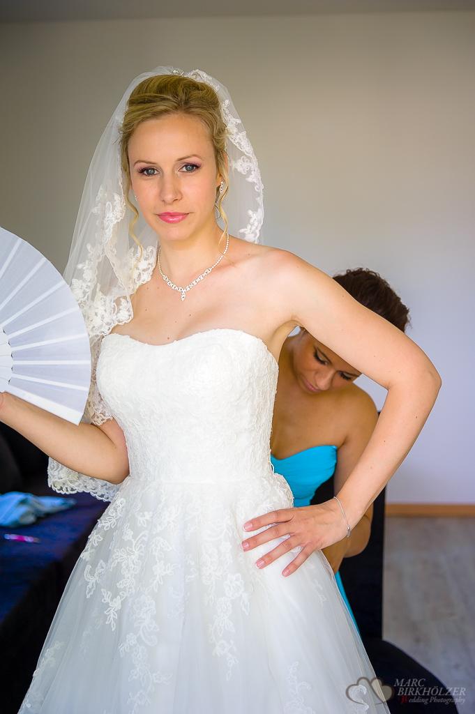 Freundin hilft der Braut beim Ankleiden fotografiert vom Hochzeitsfotograf Berlin Marc Birkhoelzer www.hochzeitsaufnahmen.com