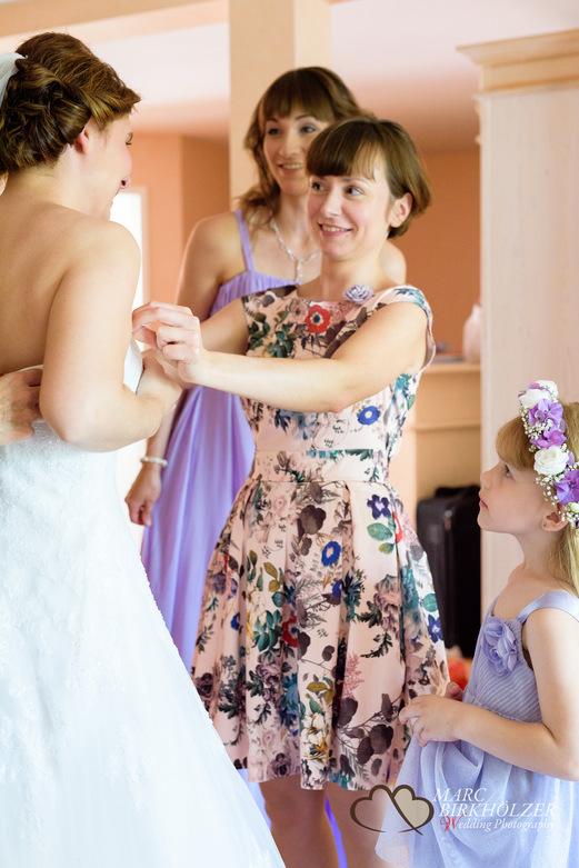 Das Brautkleid wird mit vielen helfenden Händen angezogen im Panoramahotel Uckermark aufgenommen vom Berliner Hochzeitsfotografen Marc Birkhölzer - Hochzeitsfotograf Berlin www.hochzeitsaufnahmen.com