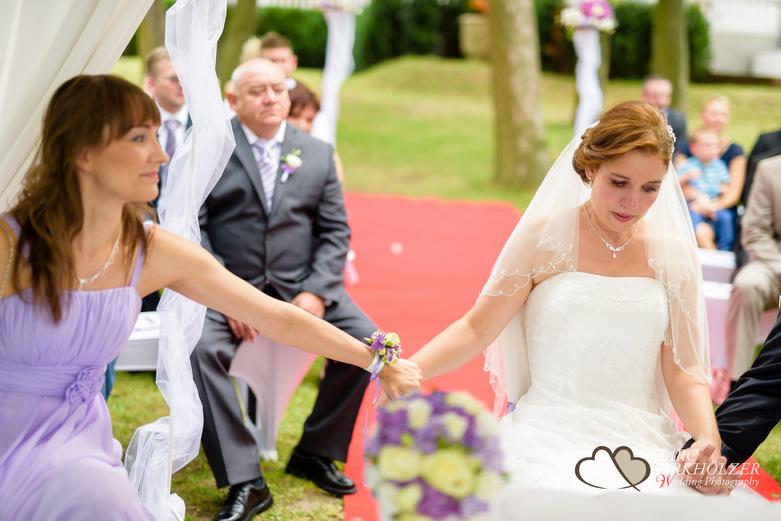 Während der Trauung hält die Trauzeugin die Hand der Braut im Panoramahotel Uckermark aufgenommen vom Berliner Hochzeitsfotografen Marc Birkhölzer - Hochzeitsfotograf Berlin www.hochzeitsaufnahmen.com